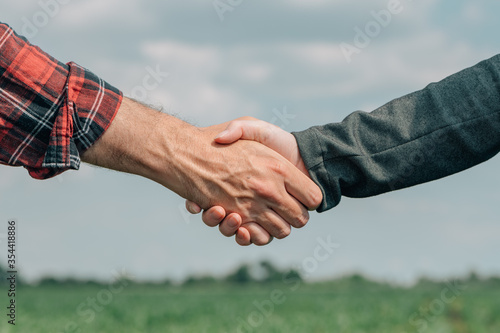 Mortgage loan officer and farmer shaking hands upon reaching an agreement Canvas Print