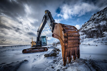 Old Excavator With Excavator Bucket In Winter. Road Construction In Snow. Lofoten Islands, Norway. High Dynamic Range HDR Image