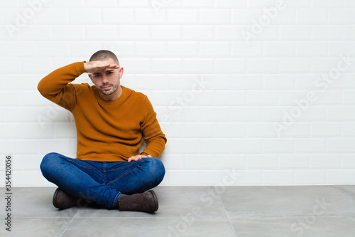 Photo young handsome man looking bewildered and astonished, with hand over forehead lo