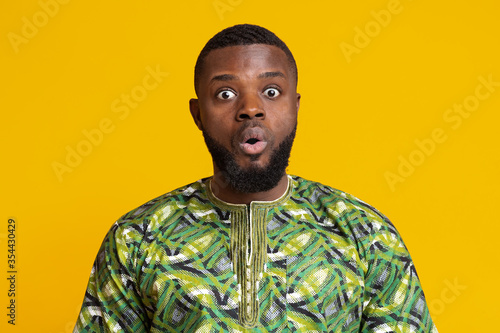 Fotografie, Obraz Stunned african man with open mouth over yellow background