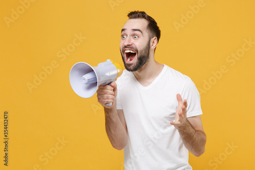 Fototapety, obrazy: Excited young bearded man guy in white casual t-shirt posing isolated on yellow background studio portrait. People emotions lifestyle concept. Mock up copy space. Scream in megaphone, spreading hands.