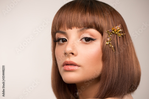 Face close up. Portrait of a woman with a bob haircut. In her hair there is a hairpin with large crystals. Makeup, black arrows and pearlescent brown shadows.