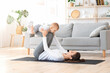 Healthy lifestyle. Young mom exercising at home with her infant baby