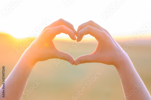 Fotomural Hands making heart shape with sunset