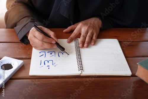 Photo Arab Muslim woman writing Arabic handwriting with ink, Arabic letters mean the n