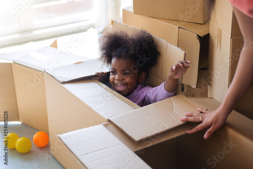 Fotografía Dark skinned child girl playing in cardboard box in room, hiding in a box while