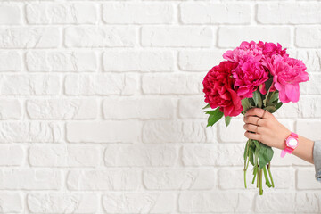 Female hand with beautiful peony flowers on white brick background