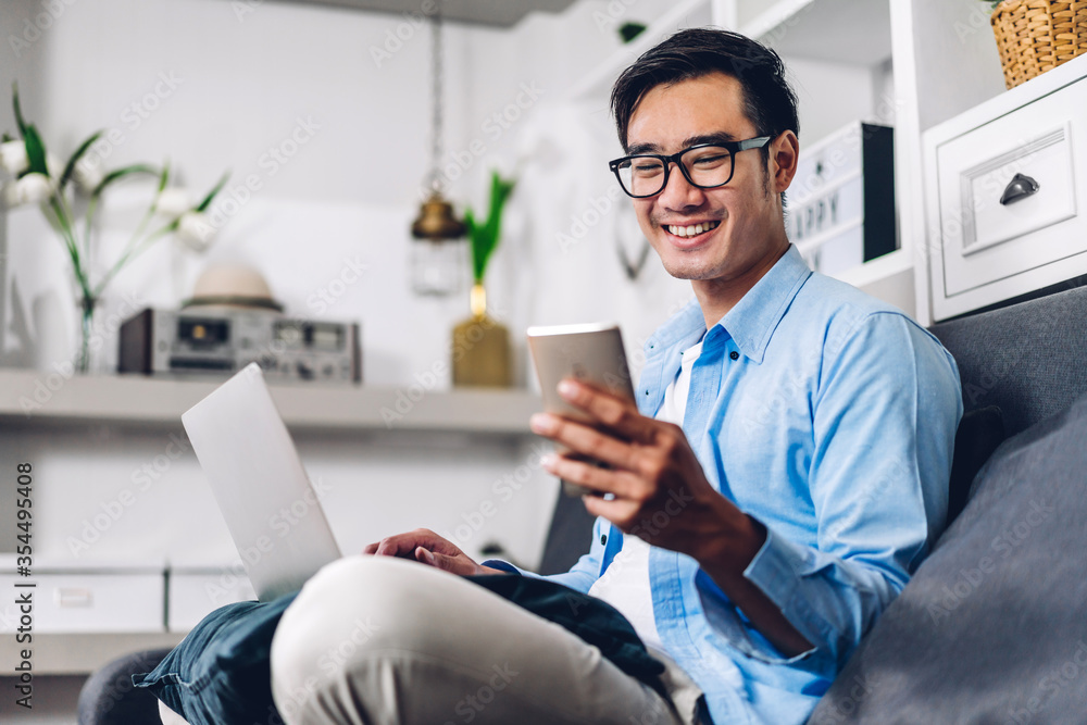 Fototapeta Young smiling asian man relaxing using laptop computer working and video conference meeting at home.Young creative man looking at screen typing message with smartphone.work from home concept