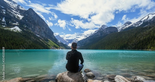 Young man looking at beautiful Lake Louise in Banff, Alberta, Canada on a blue sunny day