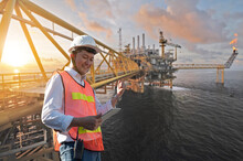 Offshore Oil Rig And Asian Worker Staff Engineer Hold Tablet