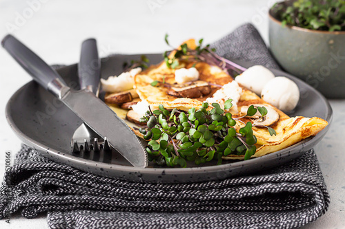 Fototapeta Classic egg omelette or omelet served with mushrooms, mozzarella and microgreens on black ceramic plate. Breakfast. Light grey stone background. Close up. obraz