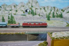 Macro Shot Of A Miniature Model Train Riding On A Bridge Surrounded By Artificial Trees And Roads