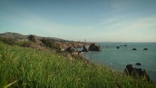 Peering Through Tall Green Grass To Reveal Rocky Big Sur, California Coastline In Slow Motion