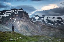 Tourist In Alps Standing In The Valley. Klein Matterhornand Furggen In The Background.