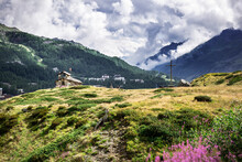 Alpine Valley In Breul Cervinia. Beautiful Meadow With Flowers. Small Church And Cross Int He Background. Church Of The Alpini.