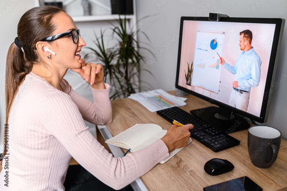 Webinars, lectures online. A woman in office is watching online classes, male teacher on laptop screen. Professional development, business training - obrazy, fototapety, plakaty