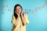 Attractive woman listening to music in headphones on color background
