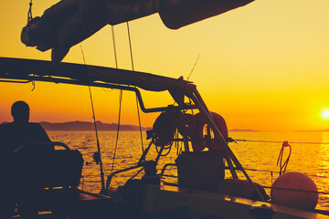Sailor steering sailing boat with a rudder in dawn / twilight time on tje open sea.