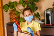 little girl with laptop. young woman holding blank sign. Coronavirus. Woman with face mask on quarantine, cooks in the kitchen at home during coronavirus crisis. Stay at home. Enjoy cooking at home.
