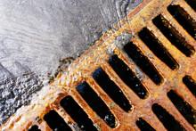 Gutter Drain. Storm Sewage During Rain. Rusty, Steel Drain Cover