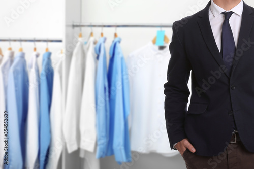 Fotografia, Obraz Businessman and rack with clean clothes at dry-cleaner's, closeup