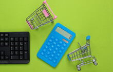 Online Shopping. PC Keyboard With Supermarket Trolleys, Calculator On Green Background. Top View. Flat Lay