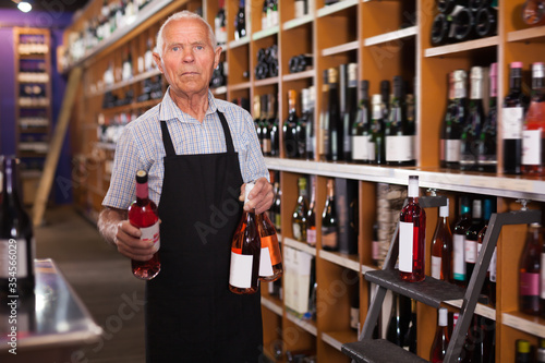 Fotomural Mature male vintner working in modern wine shop