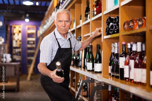 Fotografía Confident elderly male owner of wine shop taking wine bottle from shelf rack and