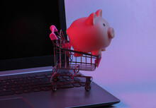 Mini Supermarket Trolley With Piggy Bank On Laptop Keyboard. Neon Gradient Red-blue, Ultraviolet Light. Online Shopping