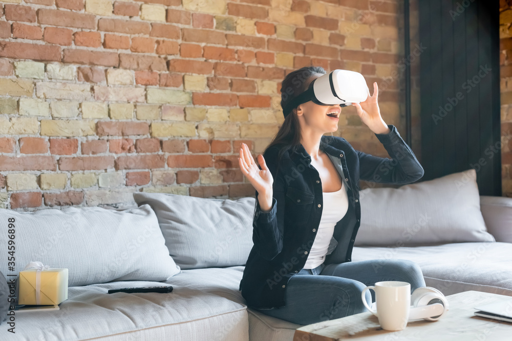 Fototapeta excited woman touching virtual reality headset while sitting on sofa
