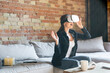 excited woman touching virtual reality headset while sitting on sofa