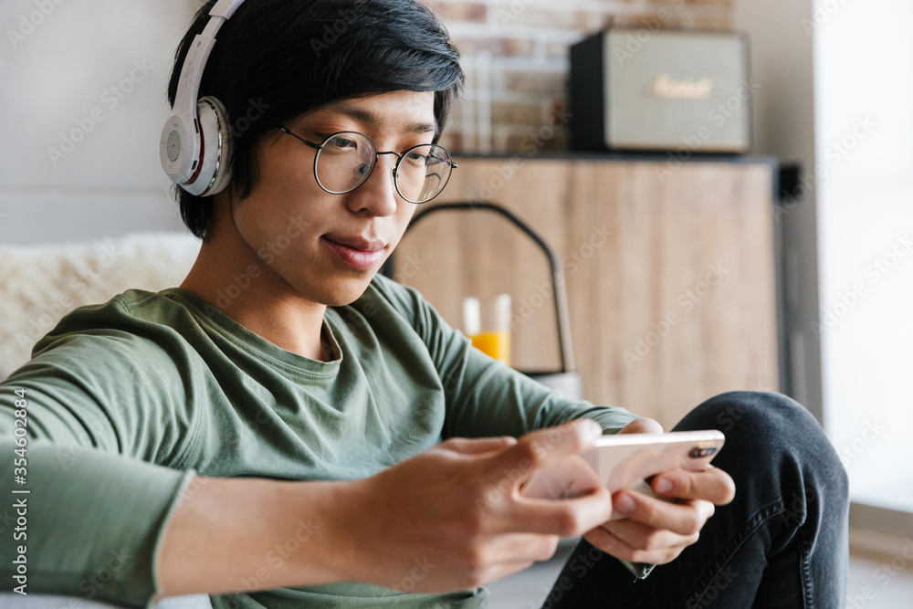 Fototapeta Image of asian man wearing headphones using cellphone in apartment