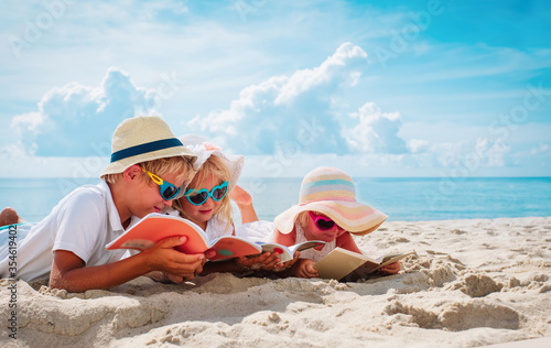 Obraz happy kids -boy and girls- read books on beach, summer reading on vacation - fototapety do salonu