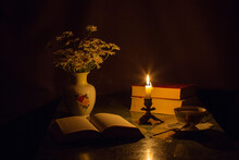 Still Life On A Black Background A Lit Candle Illuminates An Open Book, A Vase With A Bouquet Of Daisies And A Cup Of Tea