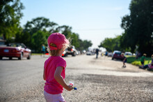 County Fair Parade With Row Little Girl Wearing Pink Picking Up Candy.
