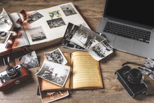 Old Family Photos And Album On Wooden Background. Vintage Pictures, Camera, Notepad And Modern Notebook Composition.