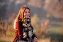 A Beautiful Girl With Red Hair Is Holding A Schnauzer Dog In Her Hands, Smiling And Looking At The Camera, Sitting On A High Stone Against The Backdrop Of A Large Mountain. Traveling With Pets