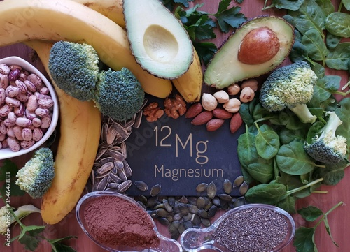 Fototapeta Foods rich in magnesium with the chemical symbol Mg for the chemical element magnesium. Natural sources of magnesium: avocado, nuts, broccoli, banana, cacao, chia, sunflower seed, spinach, beans. obraz