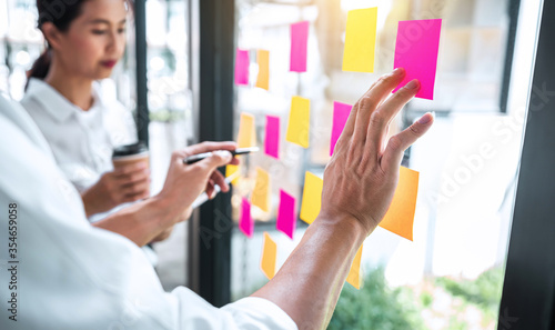 Obraz Creative team using post it notes in glass wall to writing strategy - fototapety do salonu