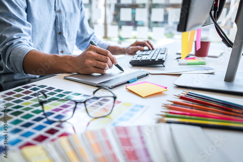 Fototapeta Image of male creative graphic designer working on color selection and drawing o