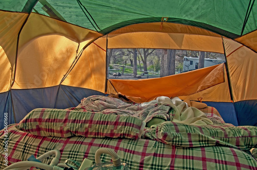 Vászonkép This camping stock photo depicts a used airbed with pillows and blankets and the air flap down to show the campsite