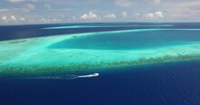 An Aerial View Shows A Motorboat Coasting Alongside A Reef In Maldives.