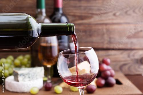 Fotografie, Obraz Red wine pouring into glass, close-up.