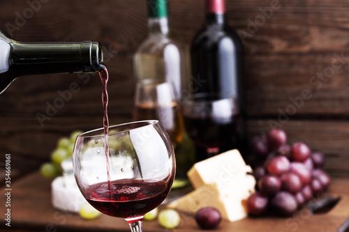 Obraz na plátně Red wine pouring into glass, close-up.