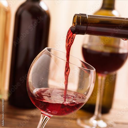 Obraz na plátně Red wine pouring into glass, close up.