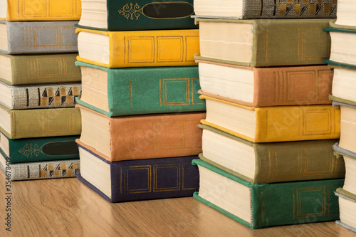 Fényképezés A stack of multi-colored old hardback books and textbooks on a shelf in a library