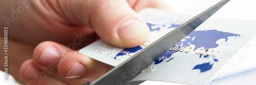 Male hand cutting banking card with scissors Canvas Print