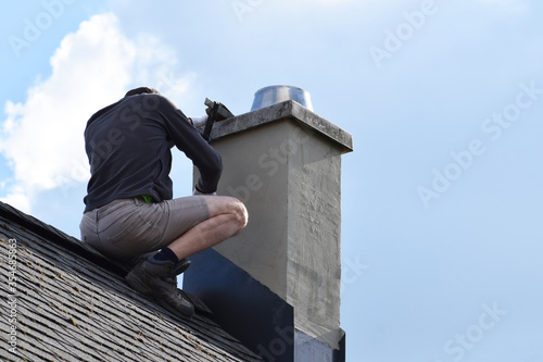 Obraz Roofer construction worker repairing chimney on grey slate shingles roof of domestic house, blue sky background with copy space.  - fototapety do salonu