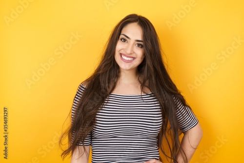 Photo Studio shot of cheerful businesswoman keeps hand on hip, smiles broadly, anticipates for surprise prepared by friends on her birthday, isolated over  background