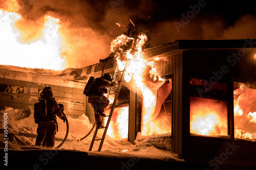 Photo Huge fire blazing in commercial building and firefighter on a roof in winter condition